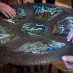 Nel Museo Rizzarda, mani toccano un'opera in ferro battuto e ceramica